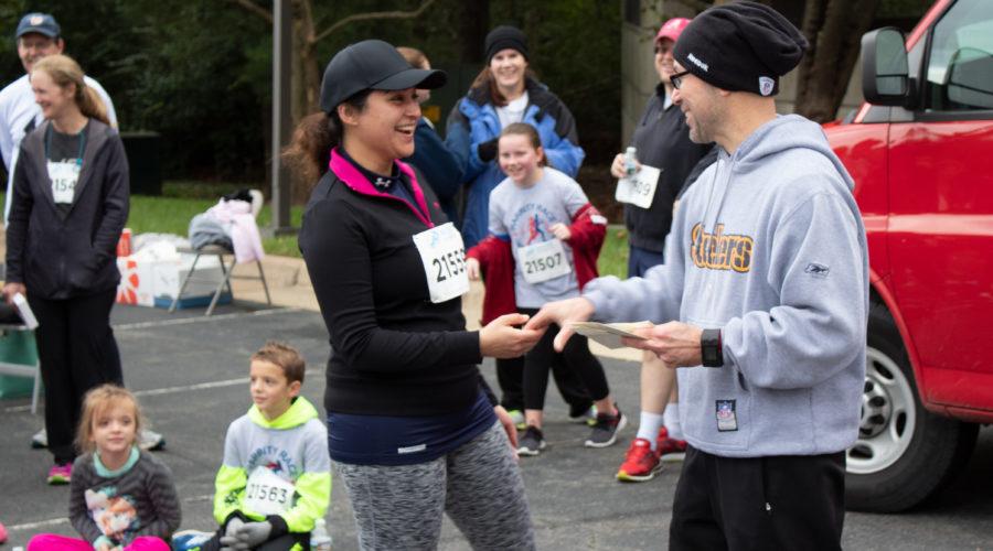 Man handing woman a prize